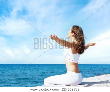 Attractive, beautiful and young girl in white sportswear meditating on a wooden pier at summer. Yoga, sport, recreation, vacation and traveling concept.