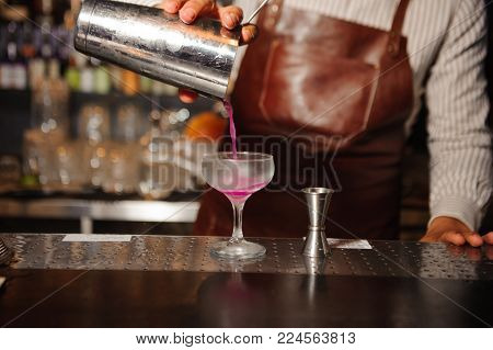 bartender in a brown apron pours from a steel shaker into a cocktail glass a lilac-colored alcohol cocktail on the bar counter