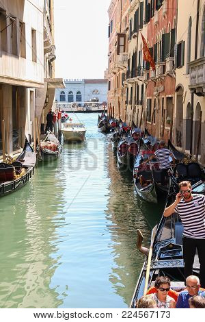 Venice, Italy - August 13, 2016: Tourists in gondola on canal of Venice
