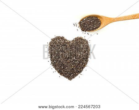 Heart shaped chia seeds and wooden spoon isolated on white background