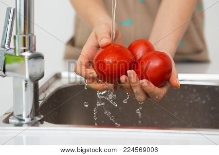 Closeup of hands washing tomatoes. Young woman cooking salad at kitchen. Cooking and organic food concept