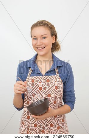 Smiling young Caucasian woman wearing apron whisking something in bowl. Beautiful housewife cooking for family. Cooking concept