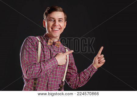 Look at this! Handsome young scientific man in vintage shirt bow tie pointing copy space and smiling while standing against black background. Education Emotios People Business concepts