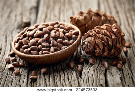 Pine nuts with cone on wooden board