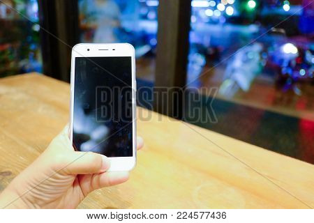 Female hand holding a white cellphone with blur wooden table atvtge coffee cafe and glass window,bokeh light at the night