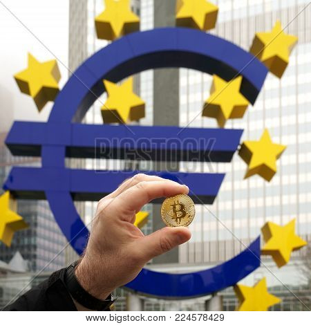 Frankfurt, Germany - January 27, 2018: Holding a Bitcoin coin next to the Euro sign sculpture in front of the Eurotower European Central Bank building in the banking district.