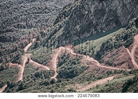 Mountain landscape: steep mountains, covered with forests, form a deep gorge, on the slope of a mountain winding road with steep turns - a mountain serpentine.