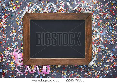 Easter background colorful crushed eggshell and blank chalkboard wooden frame top view