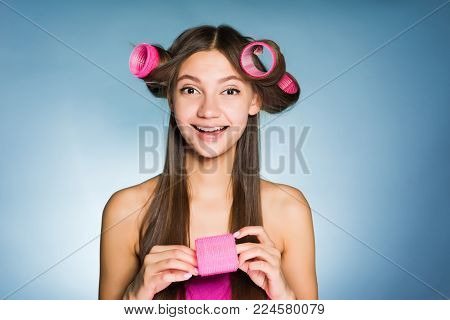 happy smiling girl doing the hairstyle with curlers and combs, laughing