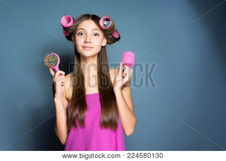 cute young girl holding a comb, on her head big pink curlers