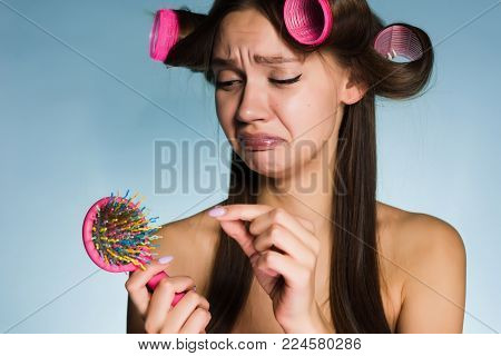 sad young girl wants a beautiful hairstyle, loses her hair, on her head curlers