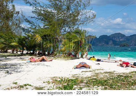 CRABI PROVINCE, THAILAND - FEBRUARY 02, 2015: Tourists relaxing on the beach of  Andaman sea at Krabi province, Thailand