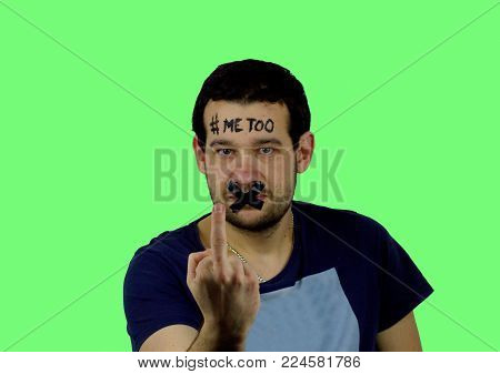 Young man with black adhesive tape on his mouth and inscription `me too` on his forehead in front of green background.The man has sealed mouth and he has raised middle finger.