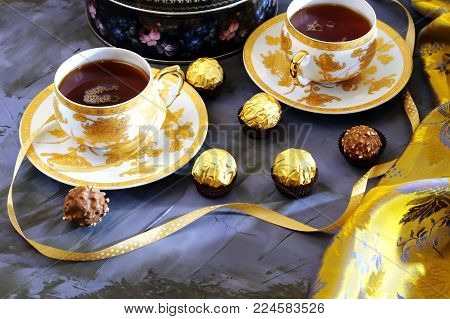 Tea ceremony, tea party. Two tea cups of gold color with black tea, candy, chocolate, cloth and box with cookies on a lilac-colored background.