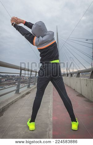 Urban jogger stretching on a big bridge.