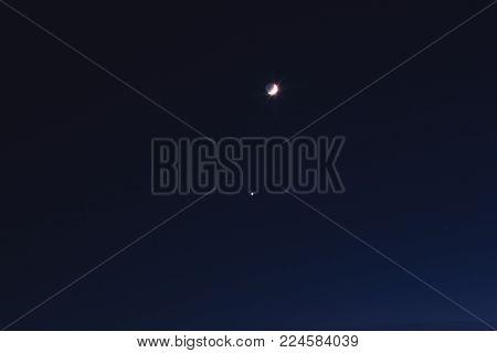 Half Moon with stars on a dark sky.
