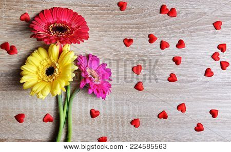 Red hearts with colorful gerbera flowers on wooden board. Valentines or Mothers day background.