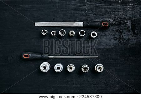 Set of tools chisel, wrenches on black wooden background. Close up. Top view. Space for your text or product display. Still life. Flat lay