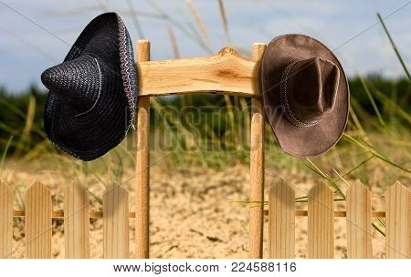 two cowboy hats and a Mexican hanging on an empty signboard in a box enclosed by a fence