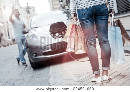 So many bargains. Selective focus on a young lady wearing casual attire carrying packages after having fun and buying many things returning to her cheerful boyfriend charging their car.