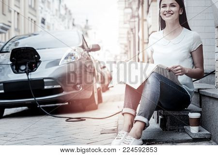 What a lovely day. Enthusiastic millennial woman looking into vacancy with a broad smile on her face while drinking coffee and waiting for her eco friendly automobile charging outdoors.