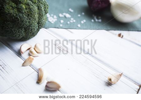 Ready to Cook Vegetarian Meal. A broccoli cabbage head, red onion and garlic cloves, blue linen napkin and white wood as a background,