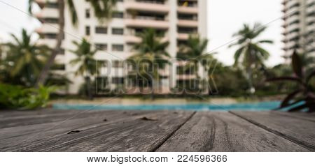 closeup of hardwood plank floor inside swimming pool and blur high building