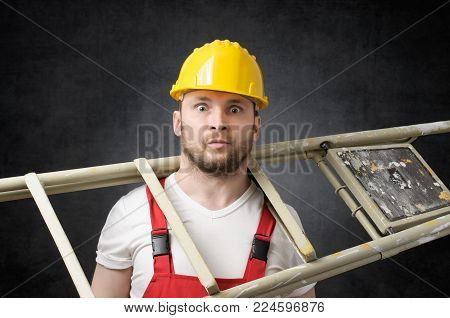 Clumsy construction worker standing with a ladder