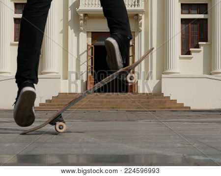 skateboarder skate & jump outdoors in front of beige building. man on skateboard. sport leisure lifesyle concept.