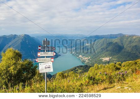 BRUNATE, ITALY - SEPTEMBER 4, 2017: Pointer on the Mountain Monte Boletto. Views of lake Como. Lombardy, Italy. The beautiful mountain scenery. Mountains, lake, pointer, and small towns.
