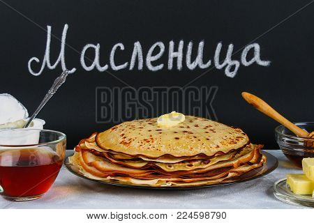 The inscription on a chalkboard in Russian: Maslenitsa. Traditional Ukrainian or Russian pancakes. Traditional dishes on the holiday Carnival Maslenitsa Shrovetide