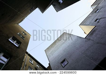 Look up at the multistory apartment house of angular shape. Empty place for text in the center.