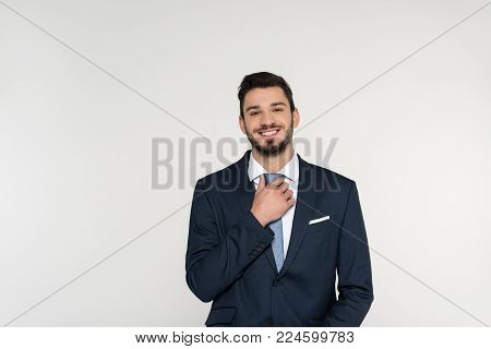 handsome young businessman adjusting necktie and smiling at camera isolated on grey