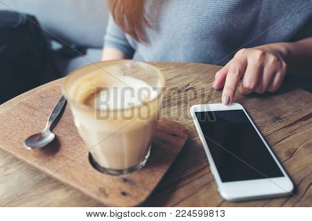 Closeup image of a woman's hand pointing finger at a smart phone with a cup of coffee on wooden table in cafe