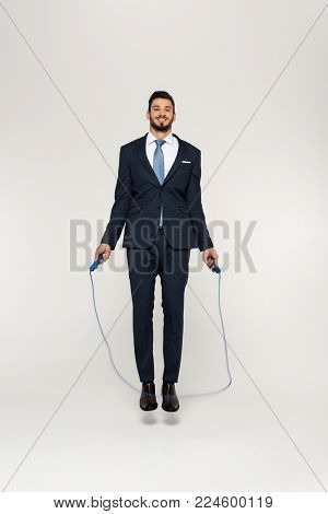 smiling young businessman jumping with skipping rope and looking at camera isolated on grey