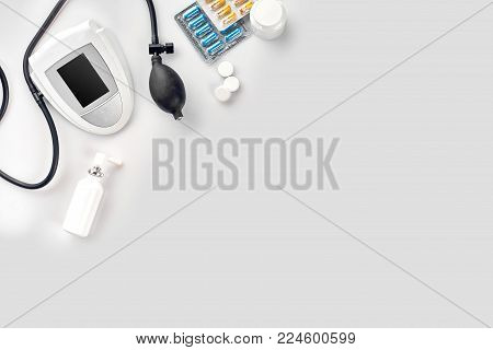 Electronic medical tonometer for measuring blood pressure and tablets in capsules on a white table. Top view. Still life. Copy space. Flat lay