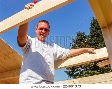 Smiling man working on rooftop in the summer