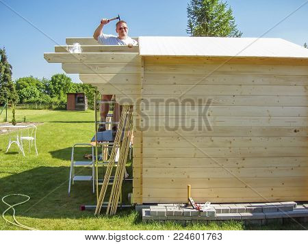 Man doing funny things while working on rooftop in the summer