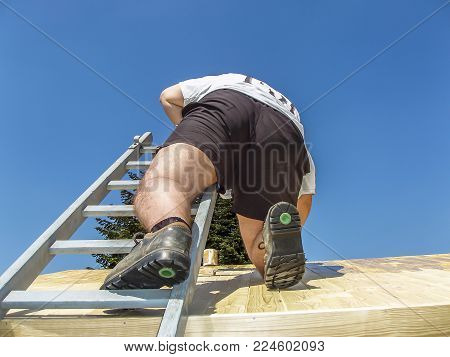 Man climbing on the roof and painting in the summer