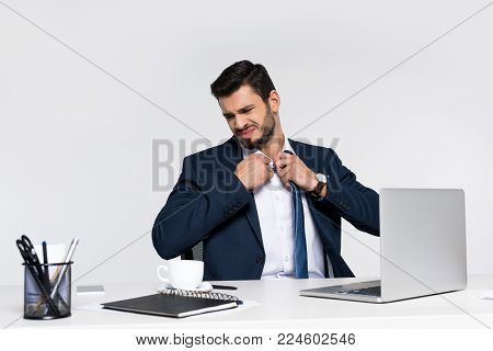 young overworked businessman adjusting necktie while sitting at workplace