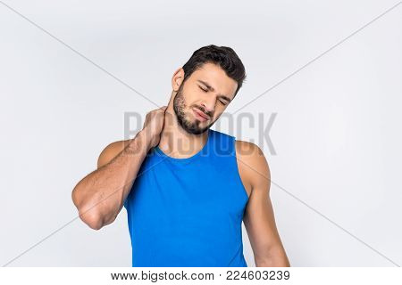 sportsman with closed eyes having backache isolated on white