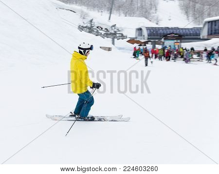 Sochi - March 29, 2017: A man in a yellow jacket is skiing and people in a ski resort in the winter in the mountains of Sochi, March 29, 2017, Sochi, Russia