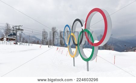 Sochi - March 29, 2017: Olympic rings at the ski resort of the Sochi Olympic Park in winter and people skiing away, March 29, 2017, Sochi, Russia