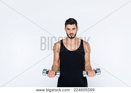young man in sportswear working out with dumbbells isolated on white