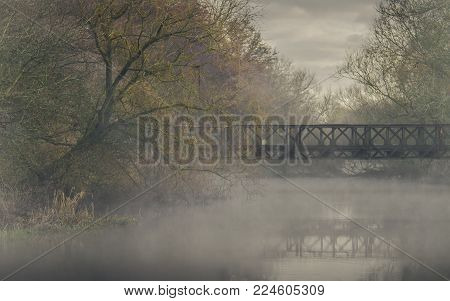 An old rusting abandoned bridge spans the misty waters of the River... a quiet and tranquil scene of an industrial nature.