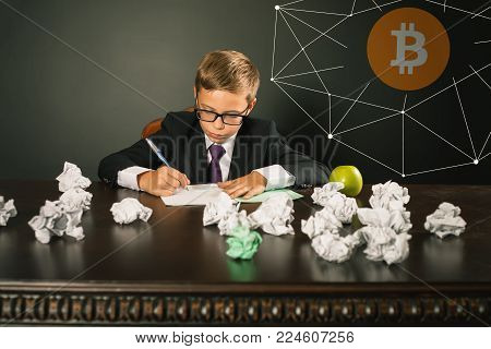 Successfully boy earning money with Blockchain technology. Future for children. Bitcoin cryptocurrency, bitcoin cash, litecoin, dash, IOTA, ethereum, smart contracts