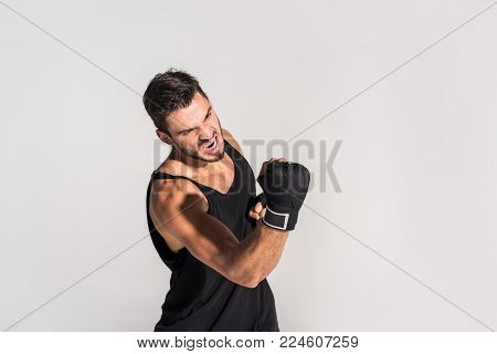 agressive screaming fighter making hit isolated on grey
