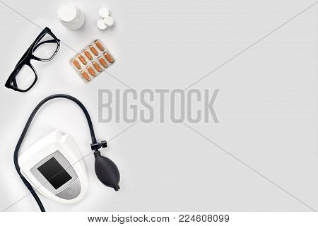 Electronic medical tonometer for measuring blood pressure, tablets in capsules and glasses on a white table. Top view. Still life. Copy space. Flat lay