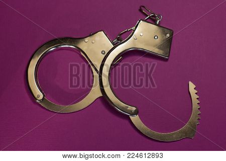 Handcuffs on crimson background (old white metal)