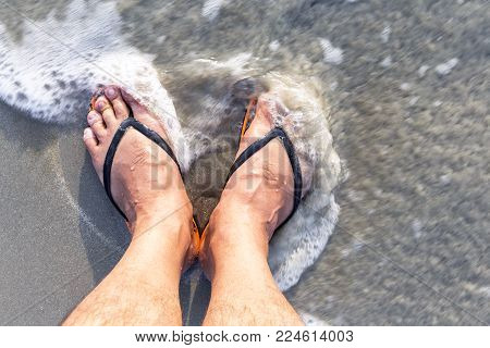 Leg of the male with wear flip flops while standing on the beach. The swash of seawater up the beach. selective focuse.